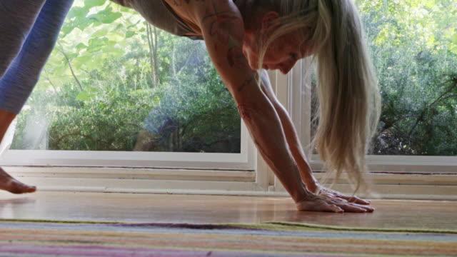 Mature Caucasian woman practicing yoga on livingroom floor