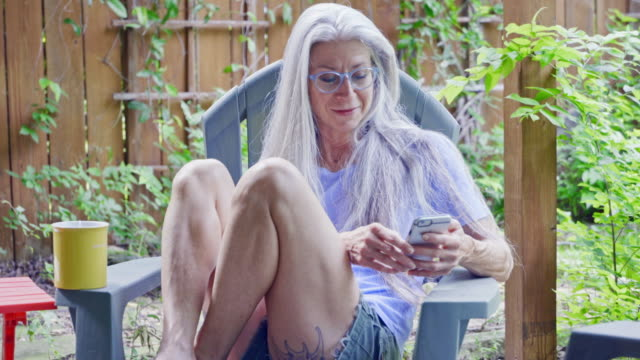 mature caucasian woman relaxing on patio texting on cell phone - stol bildbanksvideor och videomaterial från bakom kulisserna