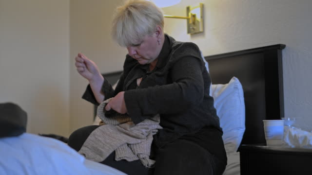 mature caucasian-white body-positive attractive woman fixing a sweater, sitting on a bed in a motel room during a journey. - body positive stock videos & royalty-free footage