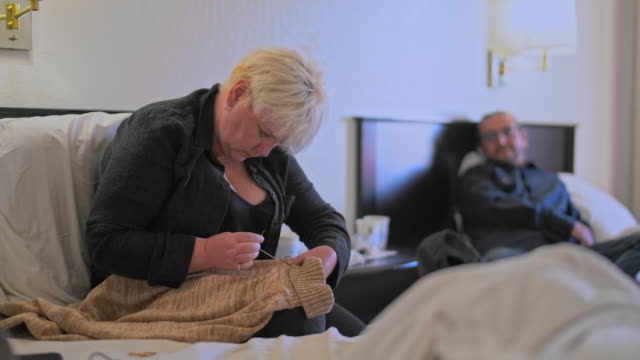 mature caucasian-white body-positive attractive woman fixing a sweater, man lying on a bed in the motel room during a journey. - body positive stock videos and b-roll footage