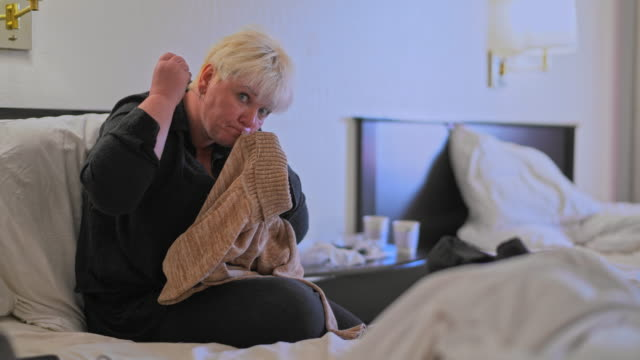 mature caucasian-white body-positive attractive woman fixing a sweater, sitting on a bed in a motel room during a journey. the man coming into the scene in the backdrop. - body positive stock videos and b-roll footage
