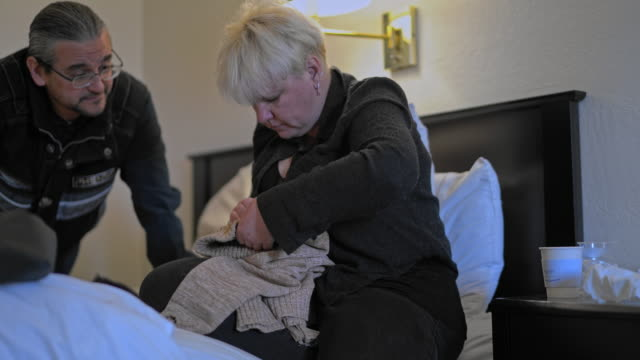 mature caucasian-white body-positive attractive woman fixing a sweater for her husband, sitting on a bed in a motel room during a journey. - body positive stock videos and b-roll footage