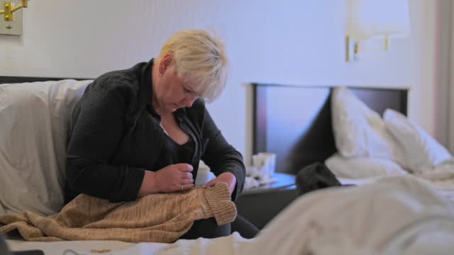 mature caucasian-white body-positive attractive woman fixing a sweater, sitting on a bed in a motel room during a journey. - body positive stock videos and b-roll footage