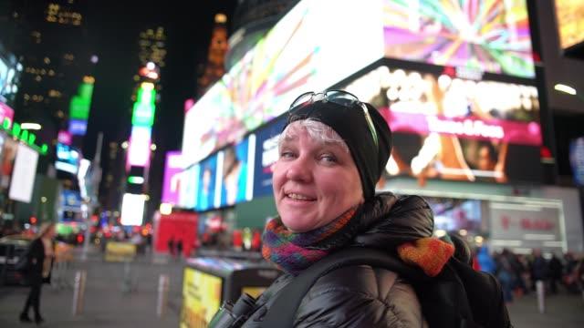 matura donna caucasica-bianca, turista, che si gode la times square illuminata a manhattan, new york city, di notte. - tourist video stock e b–roll
