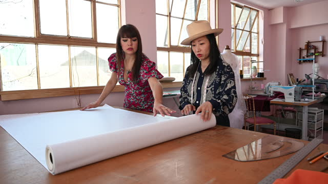 mature costume designers unrolling pattern paper in studio - workbench stock videos & royalty-free footage