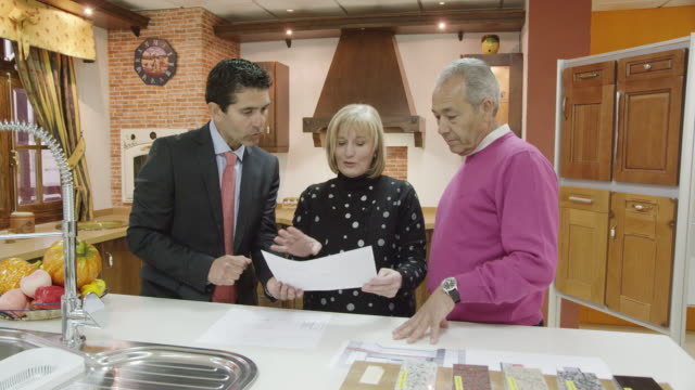 ws mature couple and salesman standing in display of traditional kitchen furniture discussing plans - verkaufsargument stock-videos und b-roll-filmmaterial