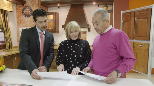 ms mature couple and salesman standing in display of traditional kitchen furniture discussing plans - verkaufsargument stock-videos und b-roll-filmmaterial