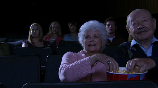 Mature couple at movie theater eating popcorn