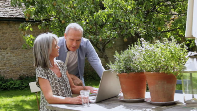ms mature couple at table in garden looking at laptop / london, united kingdom - 2010 stock videos & royalty-free footage