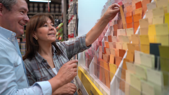 älteres paar, das farbmuster in einem baumarkt im gespräch wählt - in den fünfzigern stock-videos und b-roll-filmmaterial