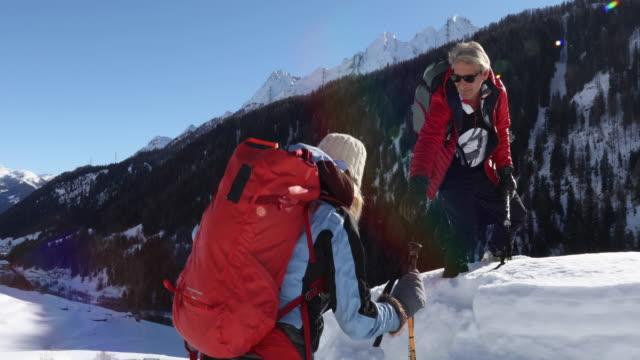 mature couple climb onto snow summit - cappotto invernale video stock e b–roll