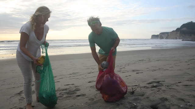 Mature couple collect garbage on expanse of beach, sunrise