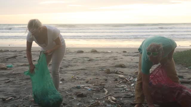 mature couple collect garbage on expanse of beach, sunrise - sopsäck bildbanksvideor och videomaterial från bakom kulisserna
