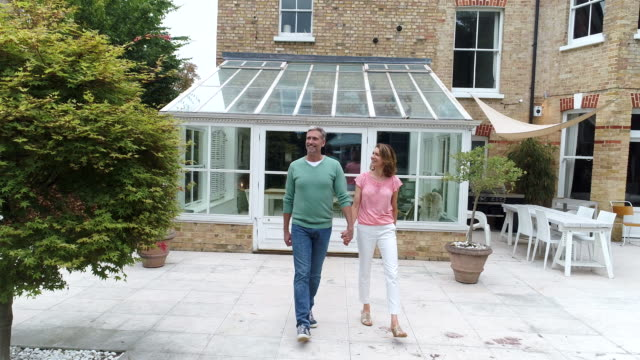 mature couple coming out of conservatory and walking across lawn holding hands - home ownership stock videos & royalty-free footage