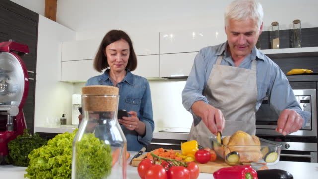 vídeos y material grabado en eventos de stock de mature couple cooking meal at home - cocina doméstica