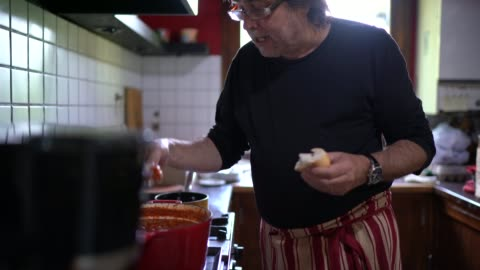 mature couple cooking pasta and tasting at home kitchen - husband stock videos & royalty-free footage