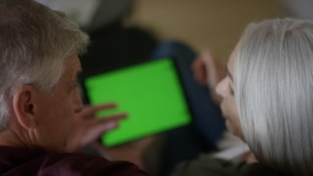 reifes paar diskutiert über digitales tablet - über die schulter stock-videos und b-roll-filmmaterial