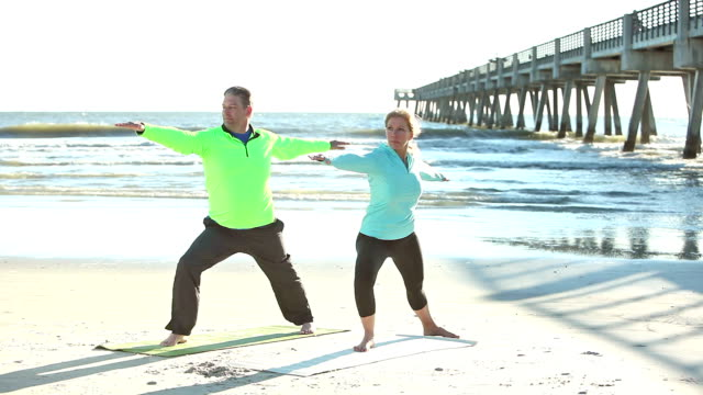 Mature couple doing yoga exercises on the beach