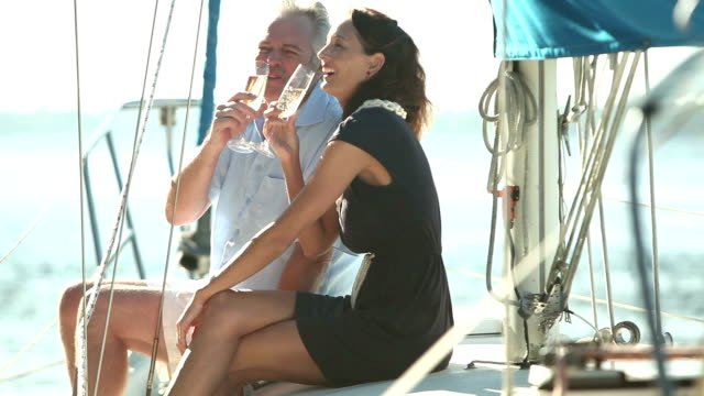 mature couple drinking champagne on deck of sailboat - wealth stock videos & royalty-free footage