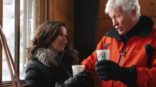 mature couple drinking coffee and talking and laughing in the lodge of a ski resort - 50 59 years stock videos & royalty-free footage