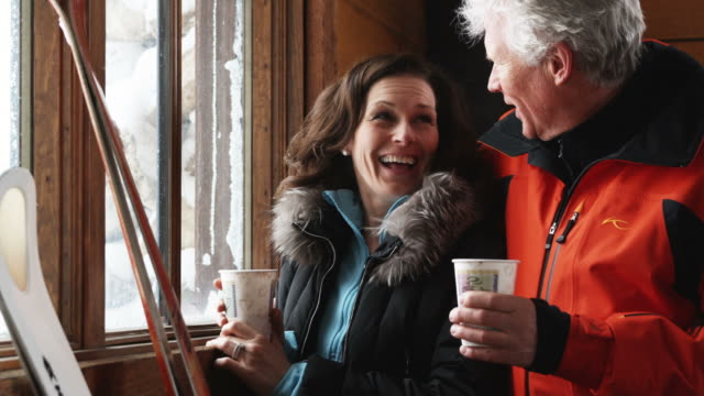 mature couple drinking coffee in the lodge of a ski resort while looking out a window - chalet video stock e b–roll
