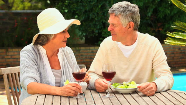 vidéos et rushes de mature couple drinking red wine in garden / cape town, western cape, south africa - couvre chef