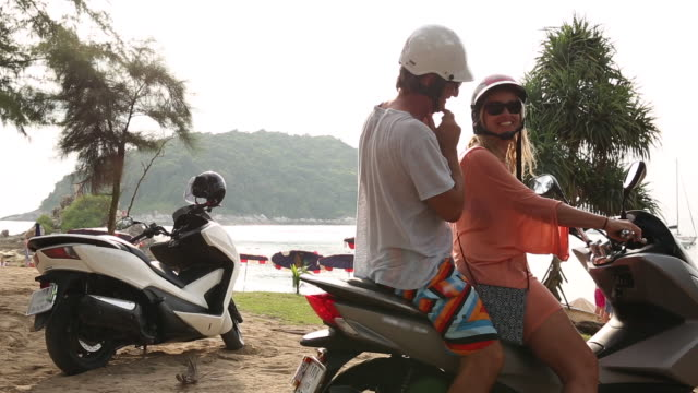 mature couple drive scooter towards beach, sea - pct stock videos and b-roll footage