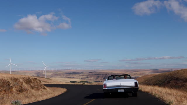 ws  mature couple driving convertible in the desert on empty road windmills in background/washington, usa - empty road stock videos and b-roll footage