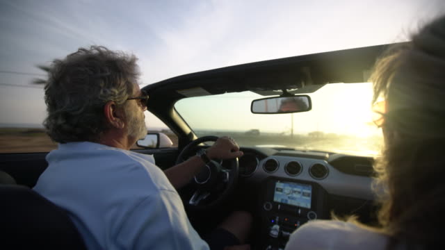 RV Mature couple driving in a convertible along the beach