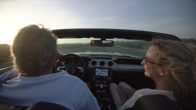 rv mature couple driving in a convertible along the beach - cabrio stock-videos und b-roll-filmmaterial