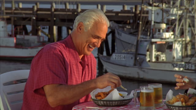 CU, PAN, Mature couple eating fish and chips in harbor, Morro Bay, California, USA,
