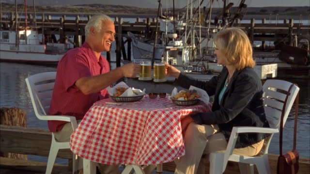 ms, mature couple eating fish and chips in harbor, morro bay, california, usa, - zwischenmahlzeit stock-videos und b-roll-filmmaterial