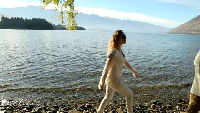 mature couple enjoy a walk along a mountain lakeshore - paar gruppierung stock-videos und b-roll-filmmaterial