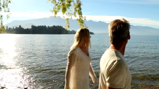 Mature couple enjoy a walk along a mountain lakeshore
