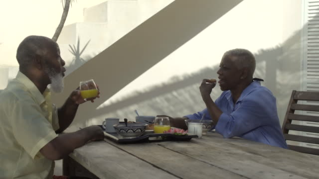 a mature couple enjoy breakfast in the sunshine - tracking shot stock videos & royalty-free footage