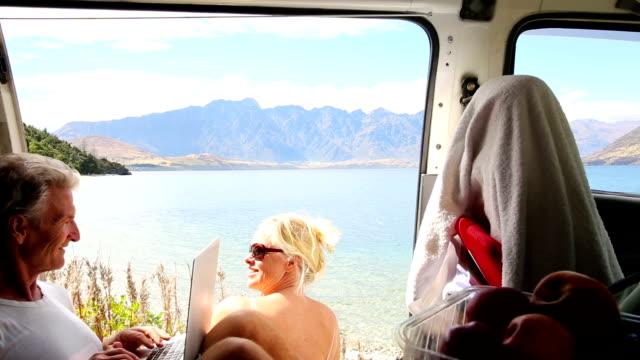 vídeos y material grabado en eventos de stock de mature couple enjoy mountain lake view from their camper-van - trailer