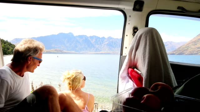mature couple enjoy mountain lake view from their camper-van - in den fünfzigern stock-videos und b-roll-filmmaterial