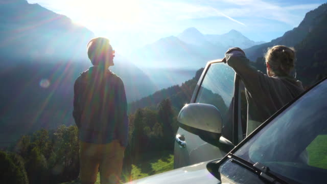 mature couple enjoy mountain view from roadside - reinheit stock-videos und b-roll-filmmaterial
