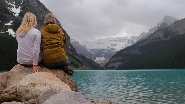 vídeos y material grabado en eventos de stock de pareja madura disfruta de la vista a través del lago louise durante la tormenta de lluvia - cabello largo