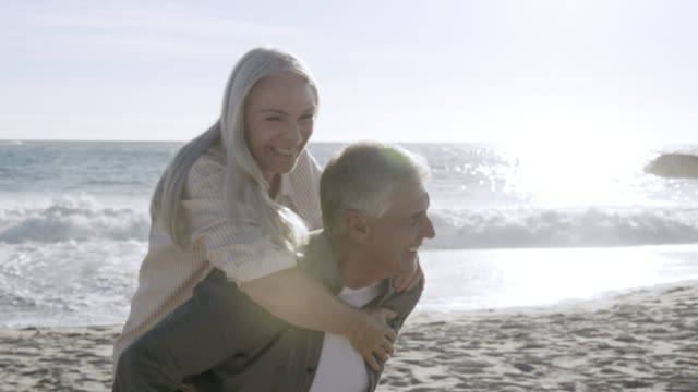 mature couple enjoying at beach during vacation - 50 59 years stock videos & royalty-free footage