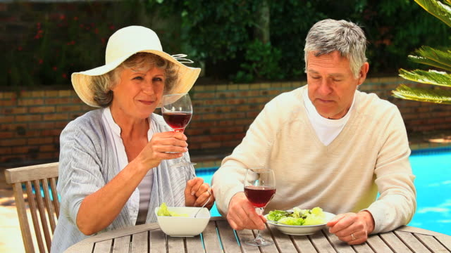 vidéos et rushes de mature couple enjoying lunch by the swimming pool / cape town, western cape, south africa - couvre chef