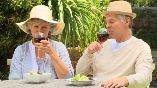 vidéos et rushes de mature couple enjoying red wine outdoors / cape town, western cape, south africa - couvre chef