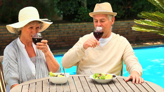 stockvideo's en b-roll-footage met mature couple enjoying wine with their lunch outdoors / cape town, western cape, south africa - bestek
