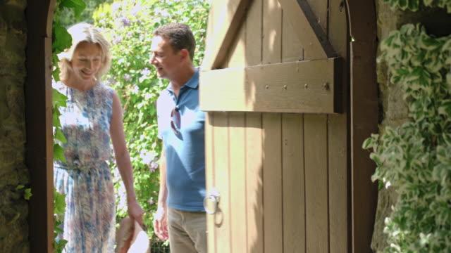 mature couple entering garden - ウィルトシャー州点の映像素材/bロール