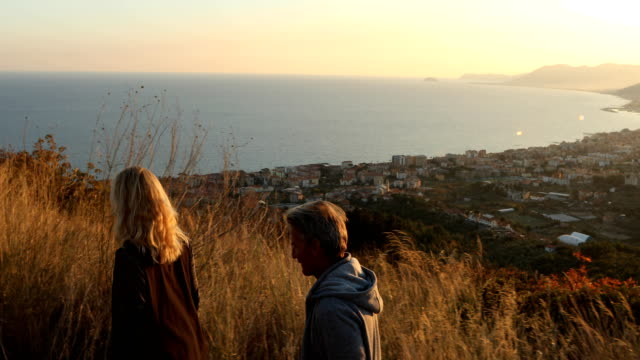 mature couple explore hilltop above mediterranean sea - coppia di età matura video stock e b–roll