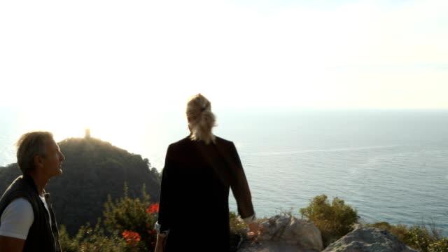 vidéos et rushes de couple senior explore la colline au-dessus la mer méditerranée - s'évader du réel