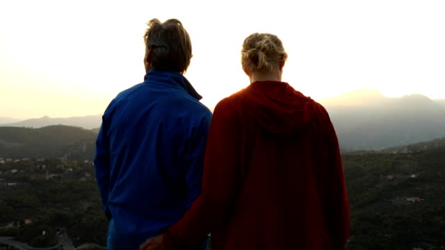 mature couple explore rocky crest overlooking hills, valley - adventure stock videos & royalty-free footage