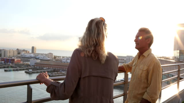 Mature couple explore seafront harbour area of city, Barcelona