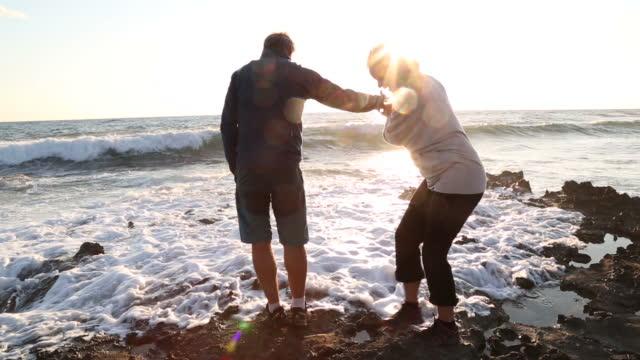 Mature couple explore tidal rocks