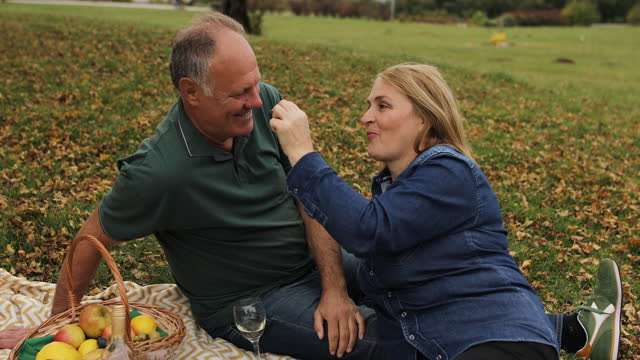 mature couple feeding each other with grapes on picnic in nature - weekend activities stock videos & royalty-free footage